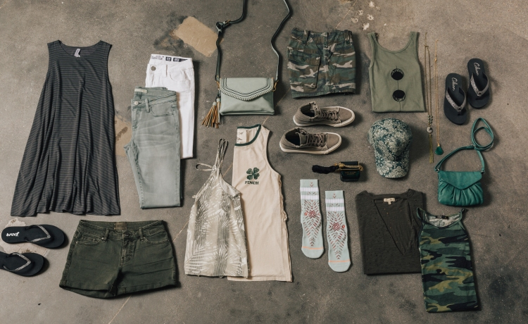 neutral lay down of pieces with St. Patrick's Day in mind: left to right, grey dress, grey and white jeans, green denim shorts, green patterned tanks, green purse, green printed socks, camo print shorts, green t-shirts and tanks, green and gold necklace