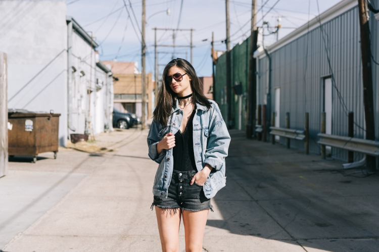 Woman in alleyway styled in oversized denim jacket, bodysuit, and black denim shorts with raw hemline.