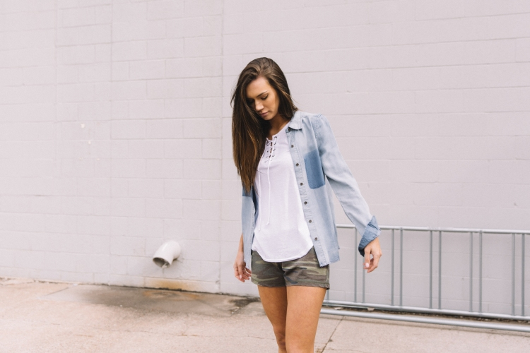 Women wearing a BKE chambray button-down top, White Crow white lace-up tank top, and french terry camo shorts.