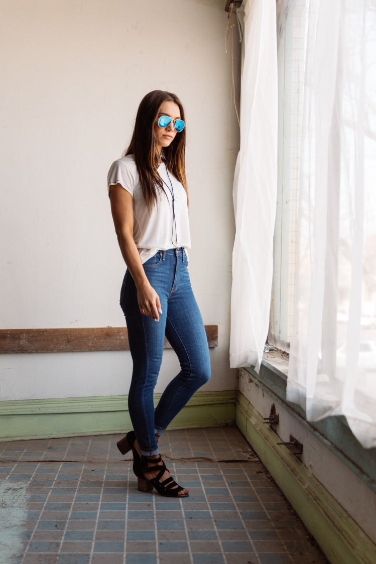 Girl in a white t-shirt and Levi's skinny jeans from Buckle.