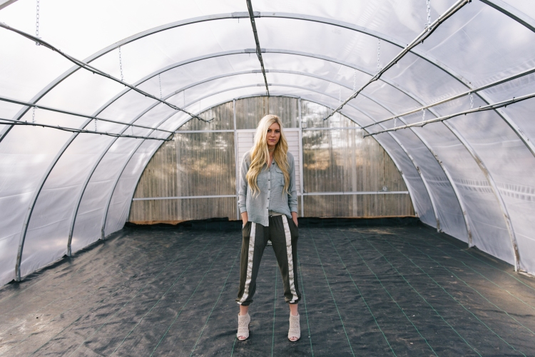 girl standing in middle of empty greehouse in green striped pants, green button-up shirt with lace backing.