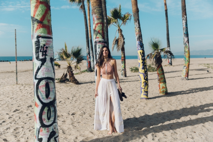 girl on beach in white walk-through maxi skirt and pink lace bralette walking between palm trees