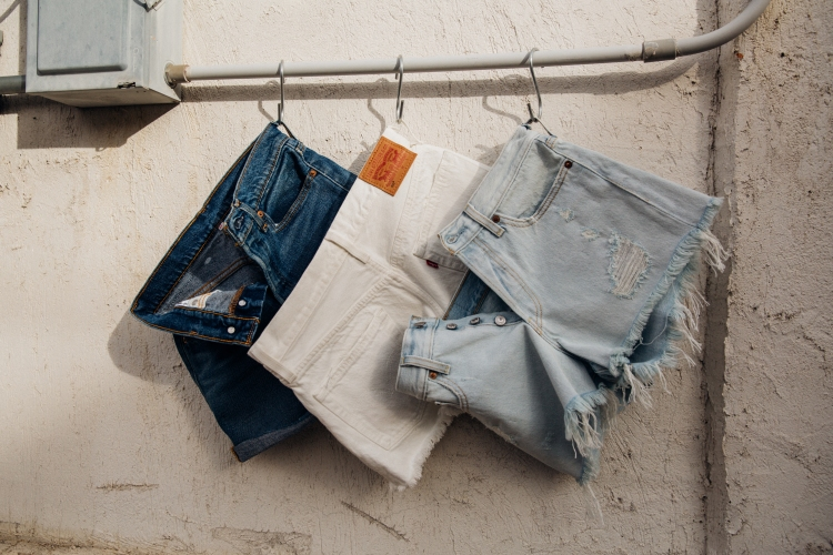 A pair of dark Levi's shorts, white Levi's shorts, and button fly Levi's shorts hanging on a bar.