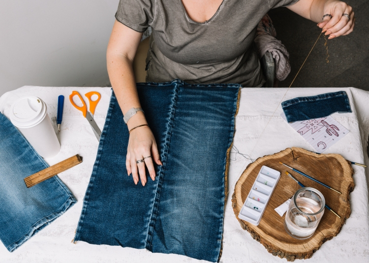 Girl cutting the denim tapestry.