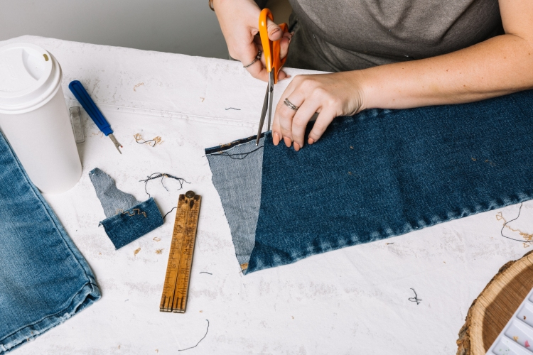 A hand steaming the denim tapestry.