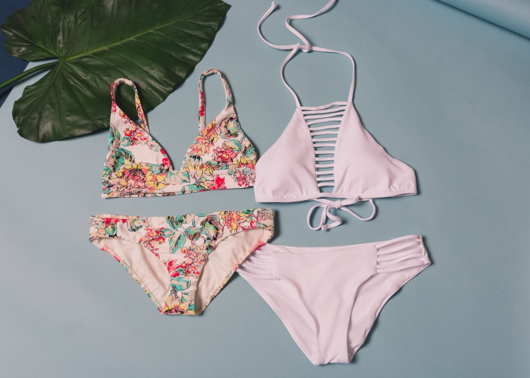 one shoulder strap bikini with white backing and pastel floral print and white strappy bikini with high, halter neckline