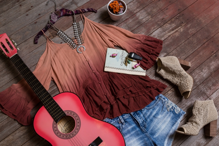 Laydown with maroon/pink ombre cold shoulder top, light wash shorts with embroidered detail, and tan block heels