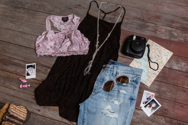 outfit laydown of destructed light-wash boyfriend fit jeans, black and maroon washed strappy tank and pink lace bralette