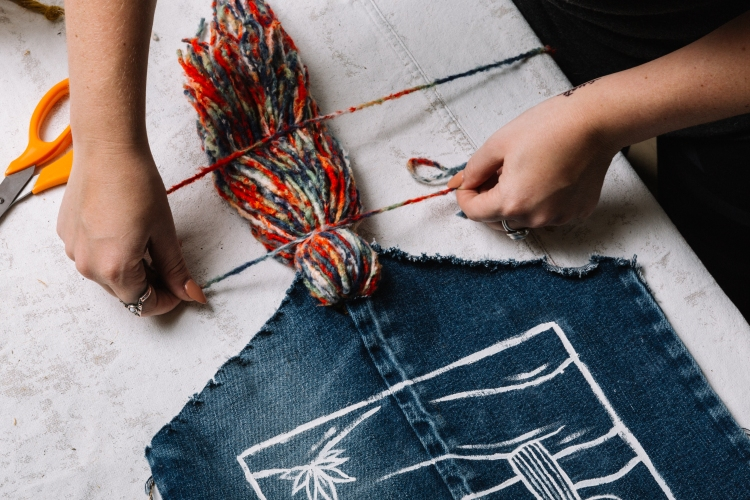 Tying tassels to the bottom of the denim tapestry.