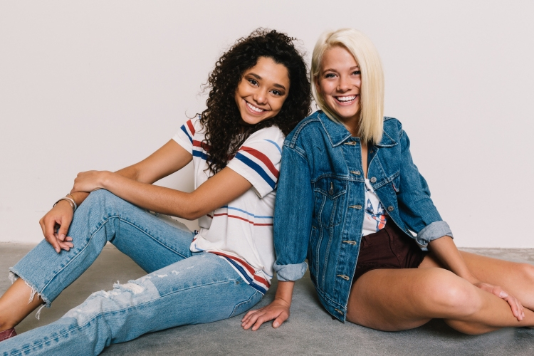 Girls sitting back to back to red, white and blue outfits. Girl on right in denim jacket and maroon shorts. Girl on left in white striped shirt and destructed light jeans.