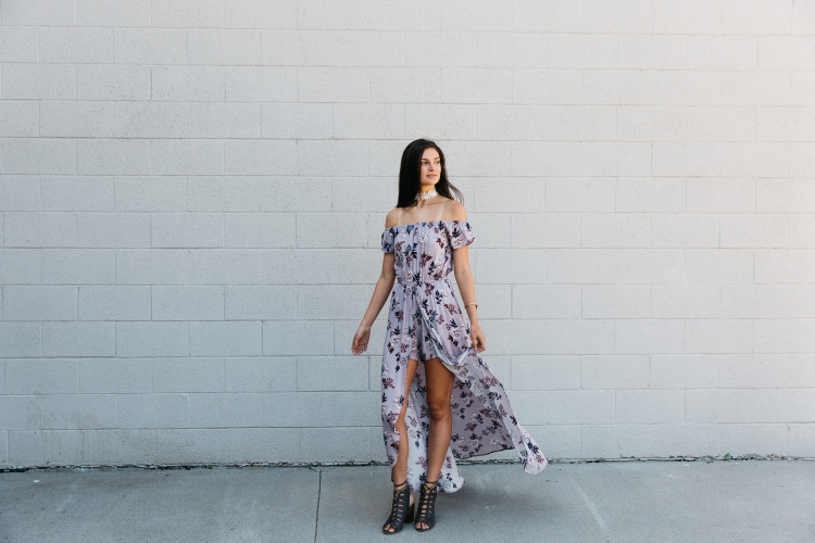 Tall woman in purple floral walk-through maxi romper. Paired with block heeled sandals.