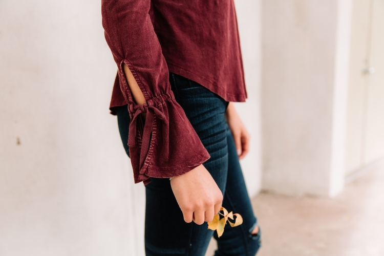 Maroon statement sleeve with bell and tie detailing.