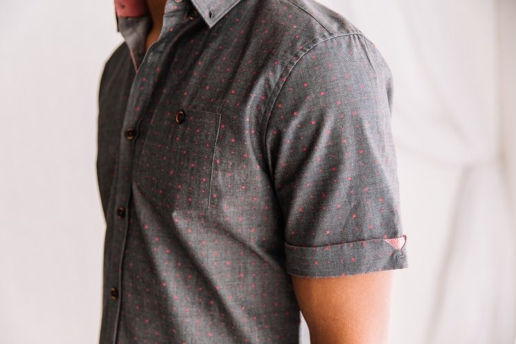 Close up shot of man in grey, short sleeved woven shirt with blush geometric pattern.