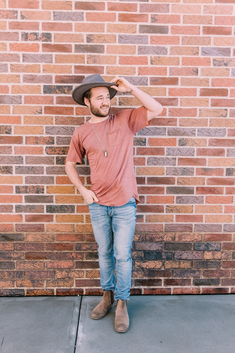 Man wearing a rust orange long-body pocket t-shirt, with a Half United bullet necklace, light wash Departwest Trouper skinny jeans, and brown Crevo Denham boots.