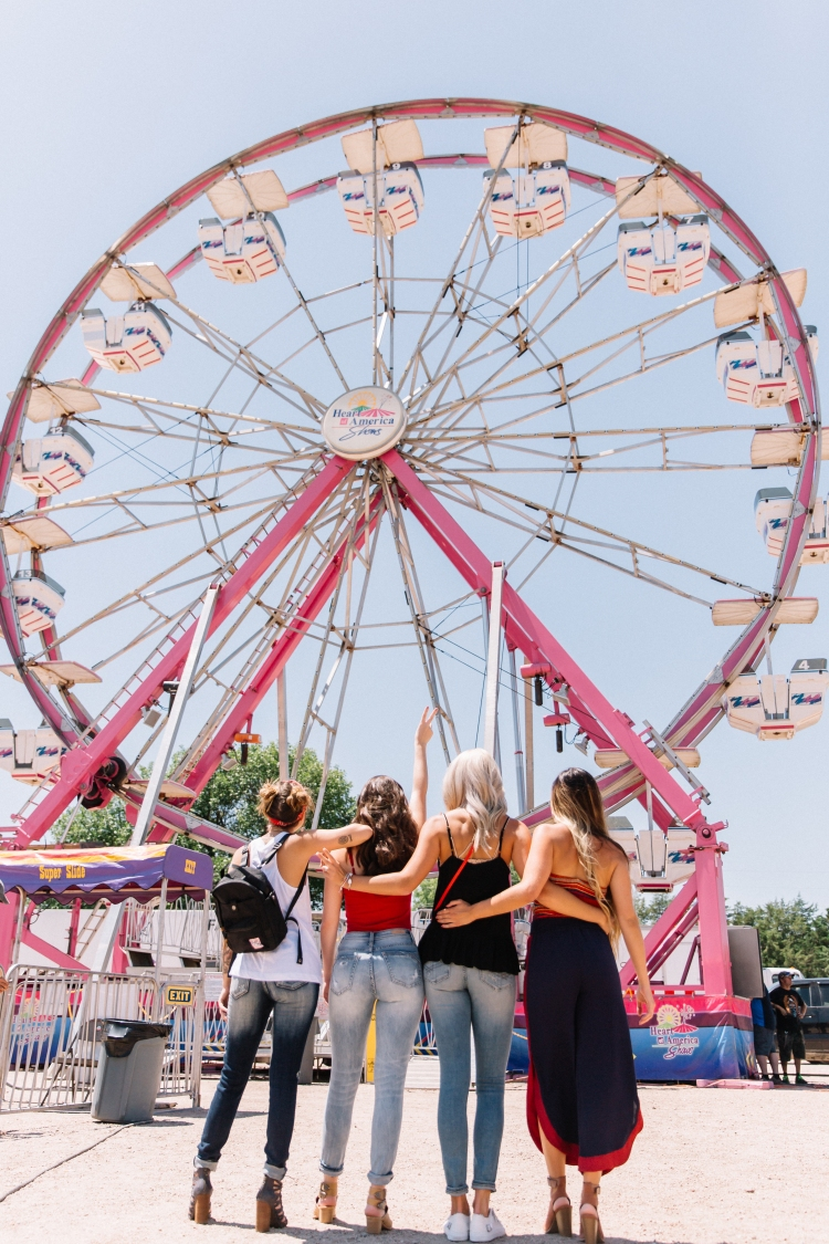 Four friends in their Buckle outfits stand with their backs toward the camera looking upward at the Farris wheel at the fair.