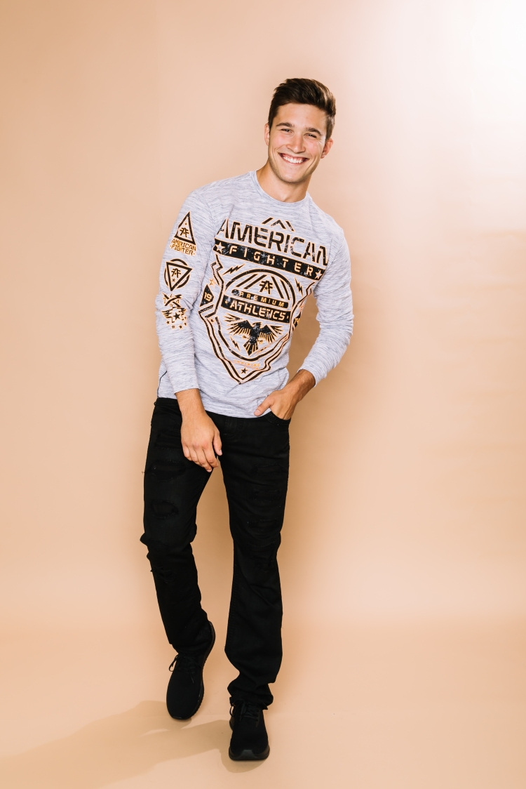 Male model wearing a graphic long sleeve American Fighter shirt with black destructed Rock Revival denim and black sneakers.