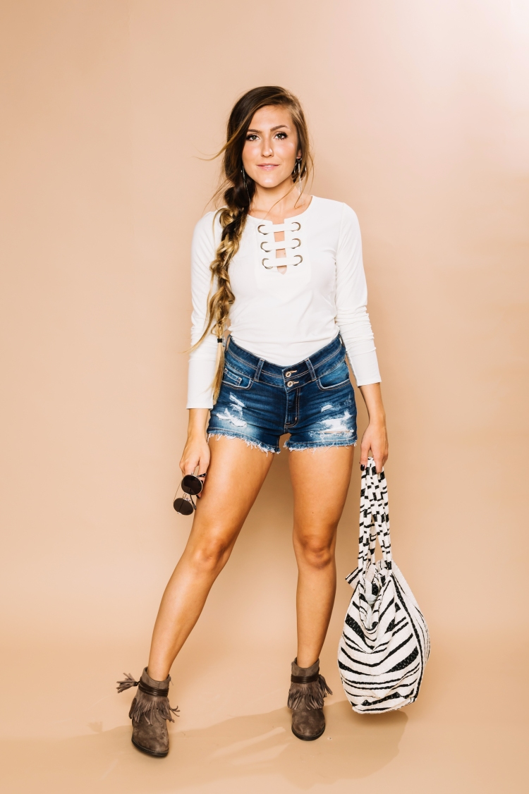 Model wearing destructed denim shorts with a long sleeve shirt paired with fringe ankle booties and accessorized with a black and white striped tote and sunglasses.