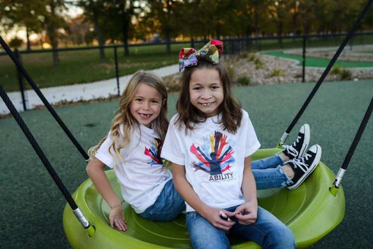 Adrianna and Skyler DeGroot on a swing together.