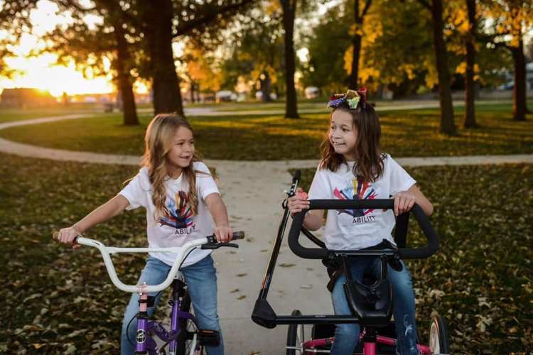 Skyler and Adrianna DeGroot riding bikes together. The sisters are both wearing the disABILITY t-shirt that was inspired by Skyler, and Skyler is riding her new bike donated to her from Josh's Rides.