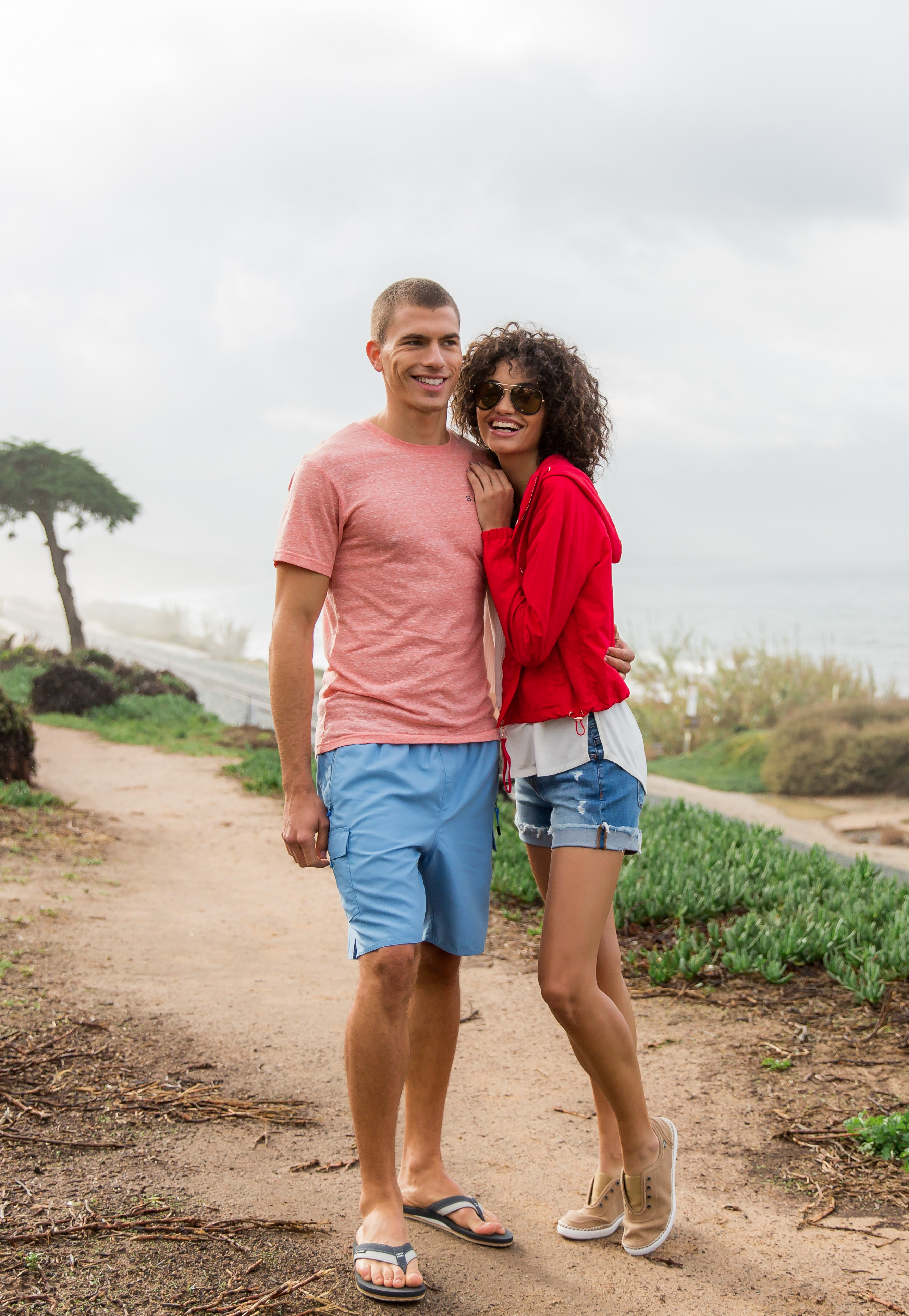 Men's and Women's Casual Vacation Outfits from Buckle featuring a Salt Life t-shirt and shorts, Kustom flip flops, white tank top, red Ashley jacket, Bridge by GLY jean shorts and Billabong tennis shoes
